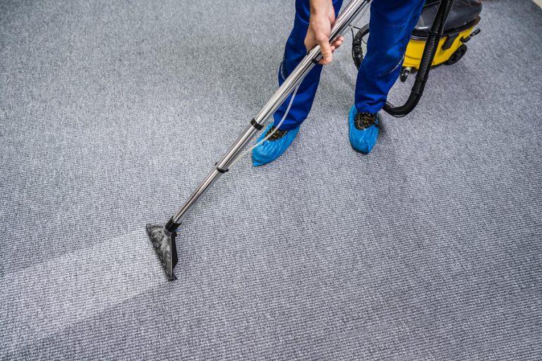 Man cleaning carpet using vacuum
